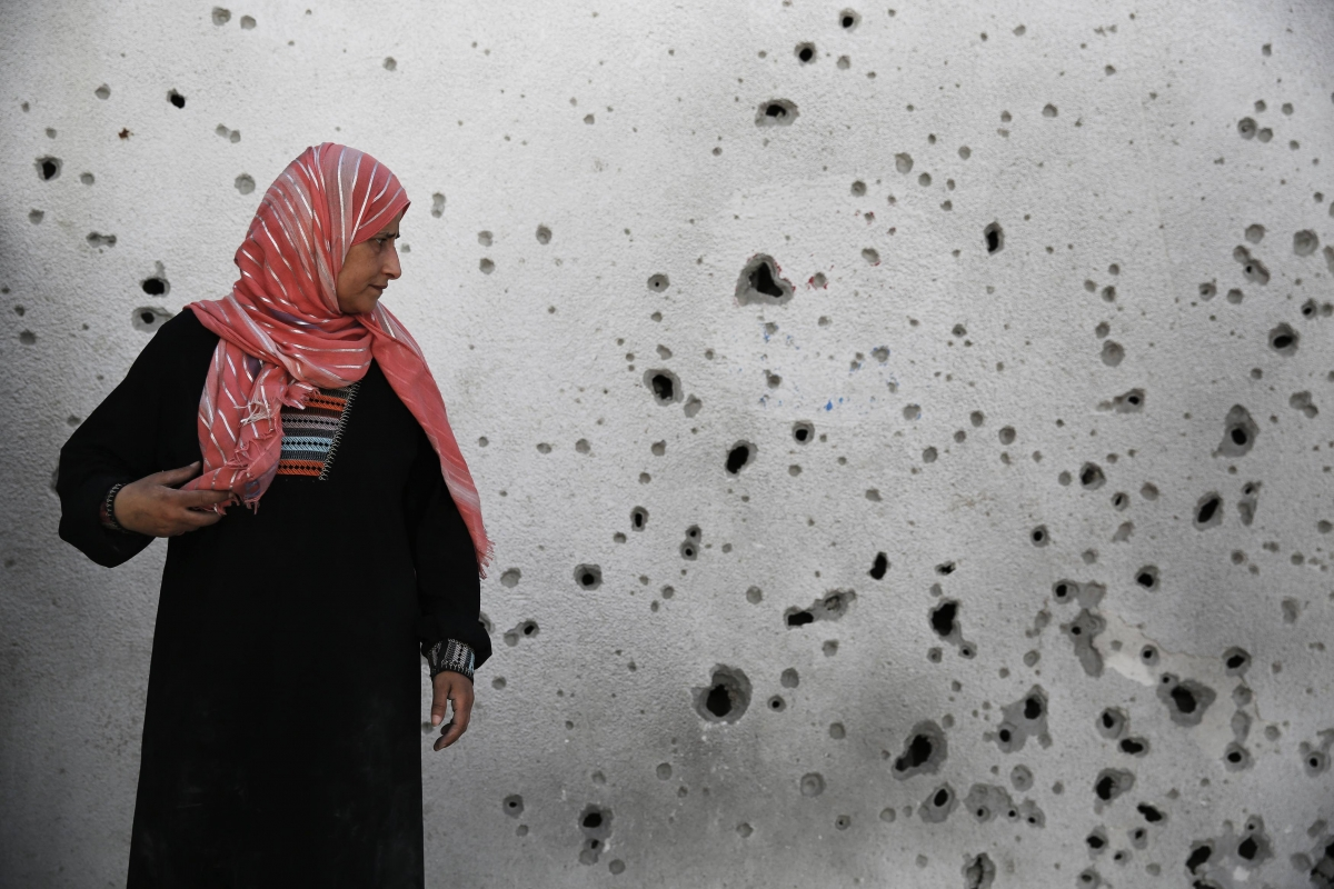 Palestinian woman looks at a shrapnel-scarred wal