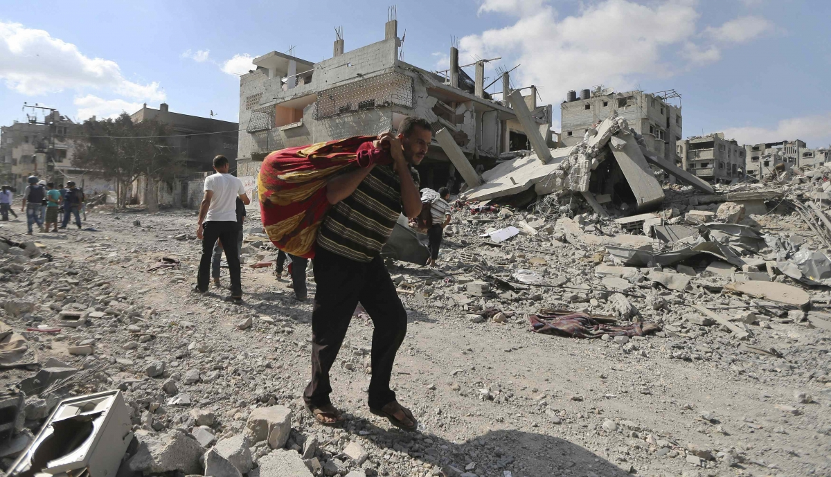 Palestinian man carries his belongings past destroyed houses