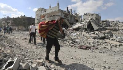 Palestinian man carries his belongings past destroyed houses