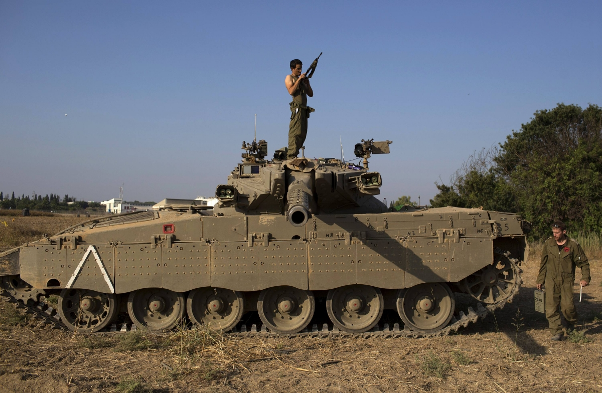 Israeli solider checks his weapon atop of a tank