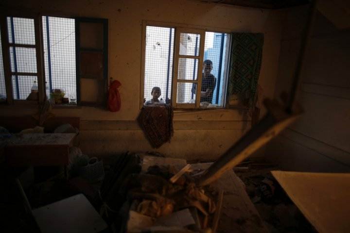Palestinians look at a damaged classroom in a United Nation-run school sheltering Palestinians displaced by an Israeli ground offensive, that witnesses said was hit by Israeli shelling