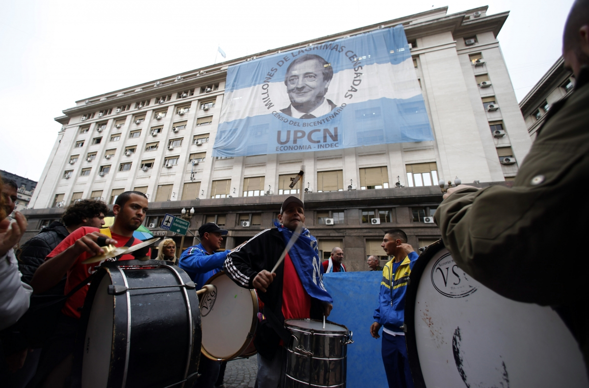 Pro-government demonstrators beat drums in front of an image of late President Nestor Kirchner placed over the Economy Ministry in Buenos Aires' financial district