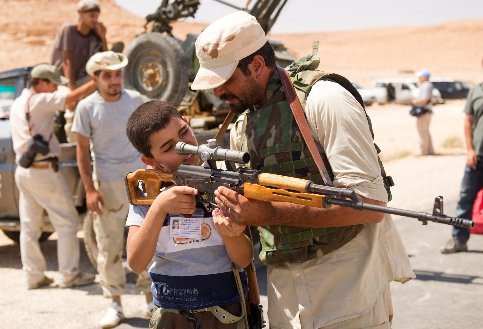 An anti-Gaddafi militant allows a boy to look through the telescopic target of his rifle near Beni Malid in 2011. (Getty)