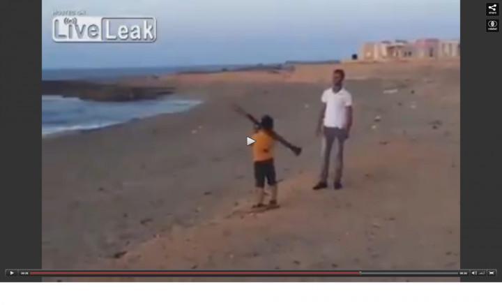 Still from the footage, showing a boy firing an RPG on a Libyan beach.