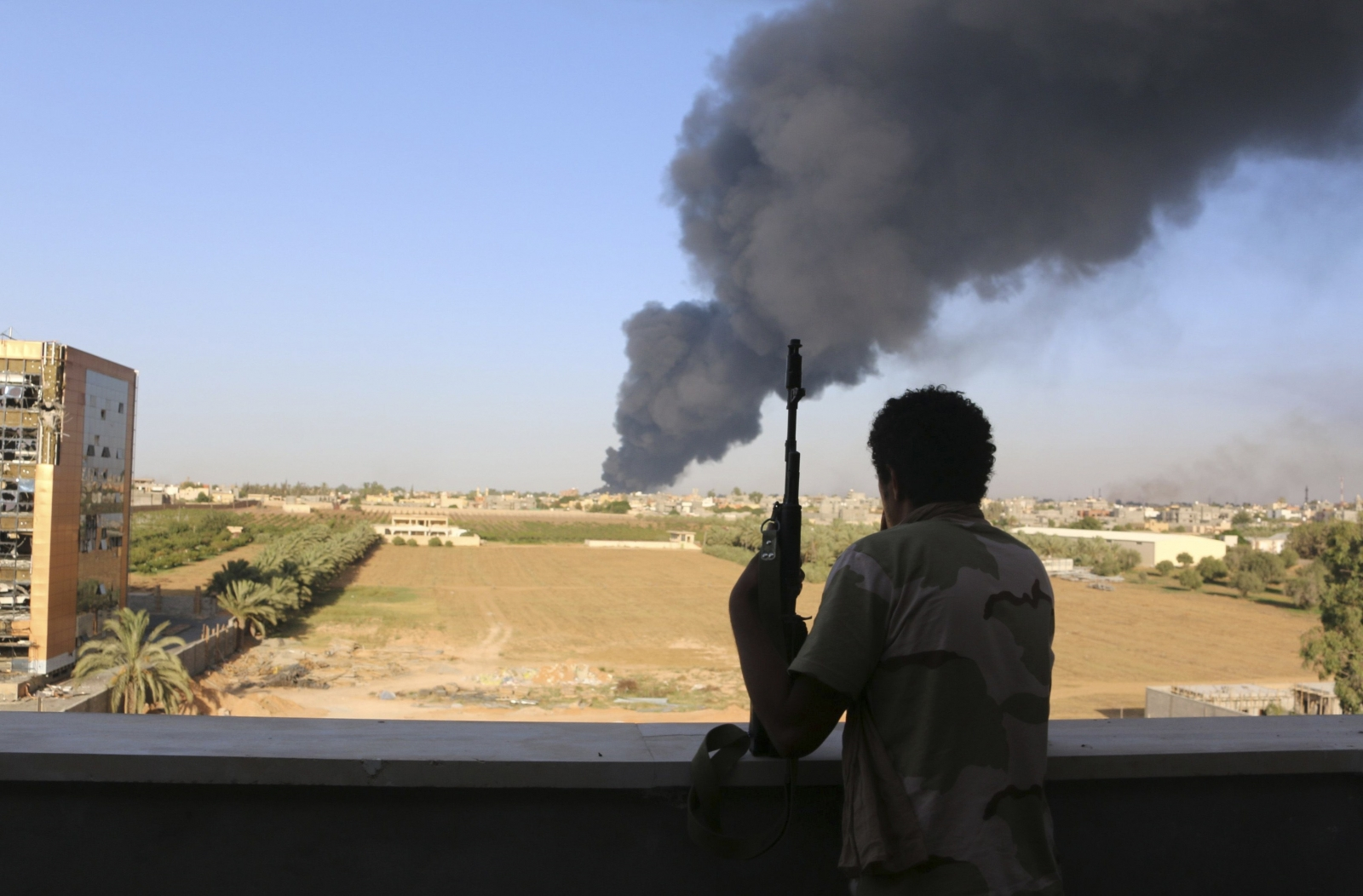 A fighter from Zintan brigade watches as smoke rises after rockets fired by one of Libya's militias struck and ignited a fuel tank in Tripoli