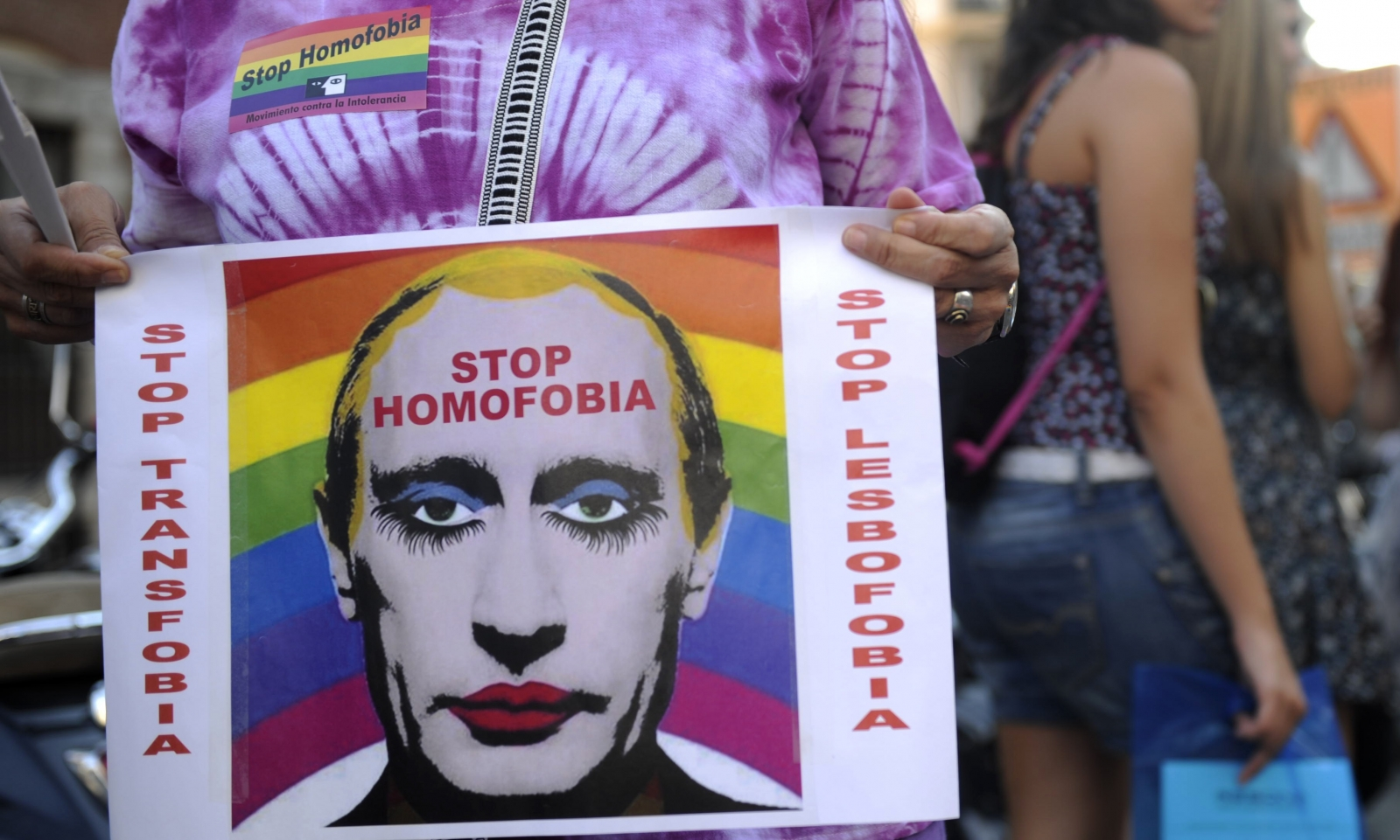 Protester holds up a picture of Putin in makeup at a Moscow gay rights rally.