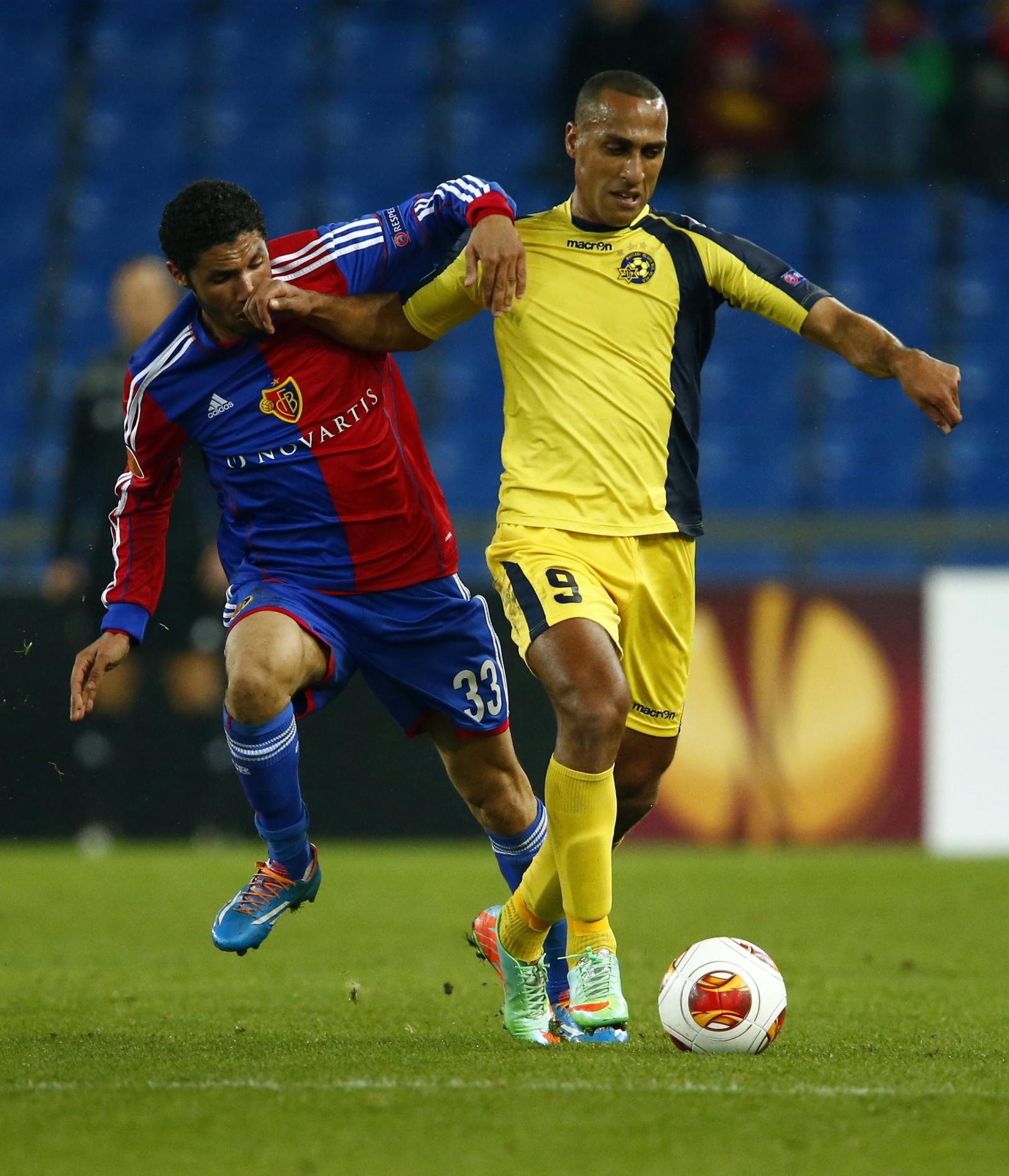 FC Basel's Mohamed Elneny (L) fights for the ball with Maccabi Tel Aviv's Maharan Radi