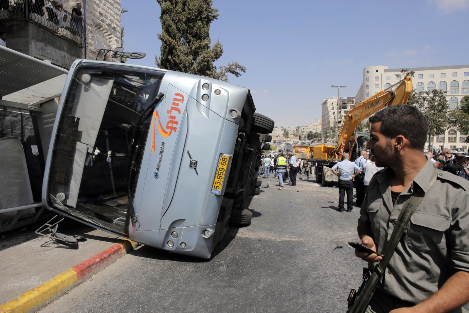 An Israeli border policeman looks at an overturned bus at the scene of a suspected attack in Jerusalem