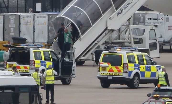 A man is escorted off a Qatar Airways aircraft by police at Manchester airport in Manchester, northern England August 5, 2014. A British fighter jet escorted a passenger plane into Manchester airport on Tuesday afterthe pilot reported that a suspect devic