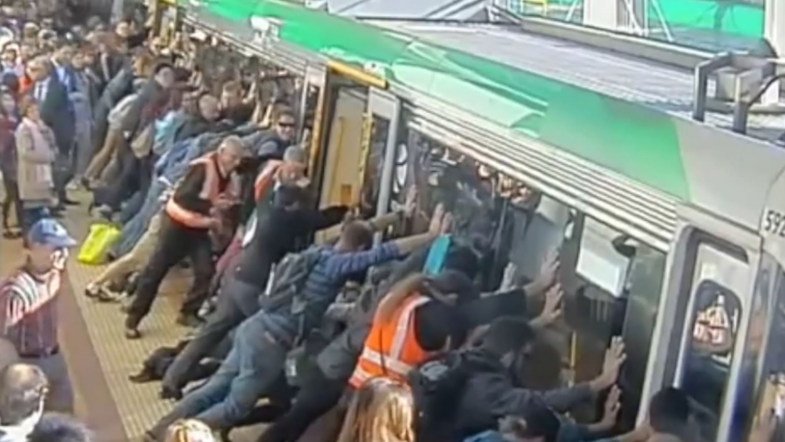 Crowd Pushes Train to Free Trapped Man
