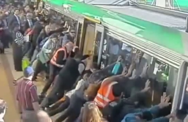 crowds pushing train to release man