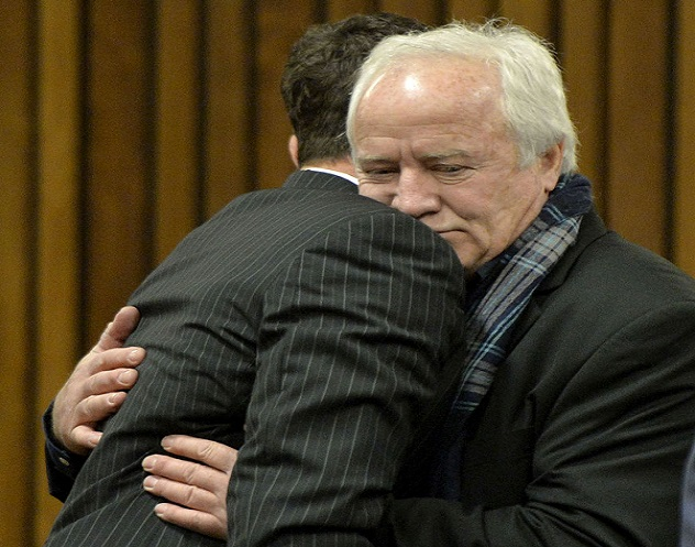 Henke Pistorius hugs his son Oscar in court during a rare appearance by the fallen idol's absent father