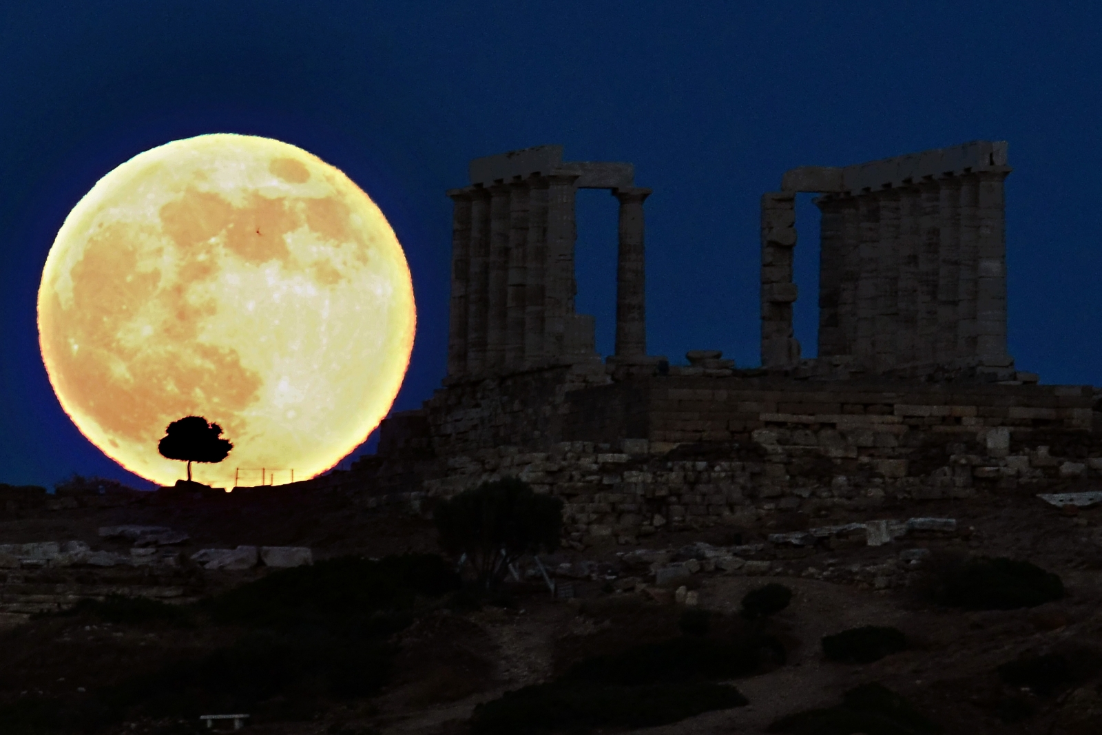 supermoon next to Greek temple