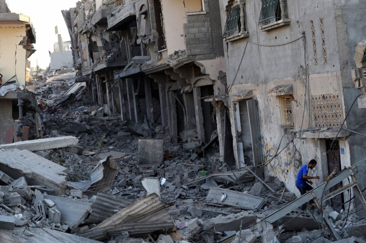 A Palestinian man enters his partialy destroyed home in the devastated neighbourhood of Shejaiya in Gaza City (Getty)