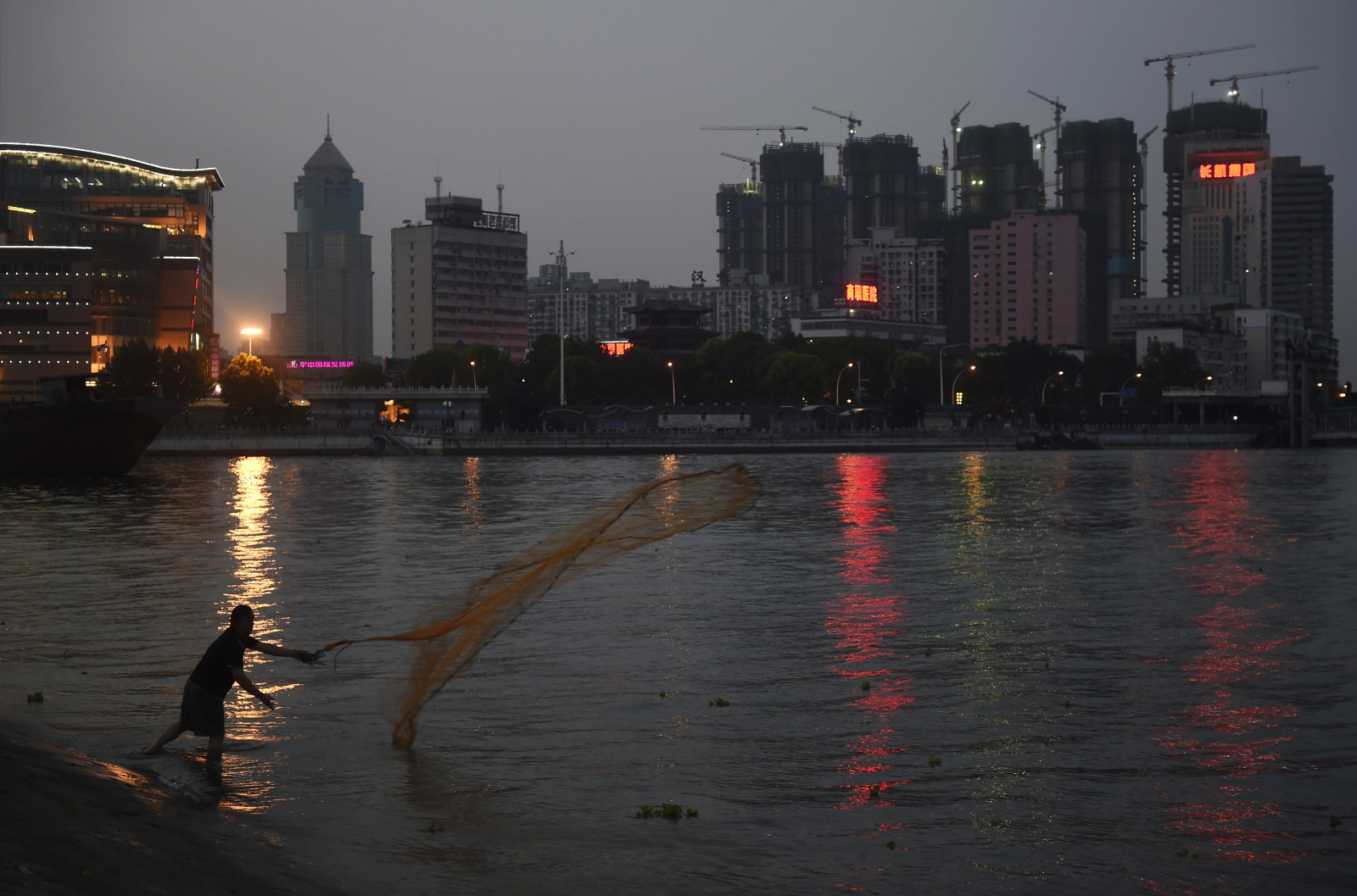 A man casts a net by the side of a river next to a construction site of new residential buildings in Wuhan, Hubei province.