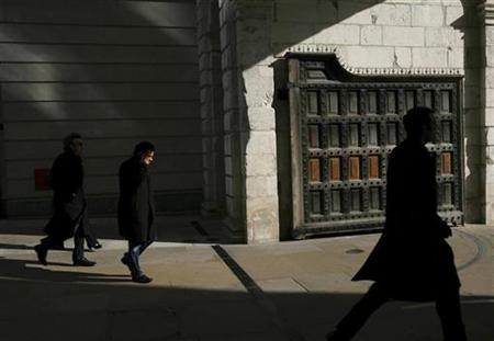 Pedestrians walk through the gate at Paternoster Square, home to the London Stock Exchange, London