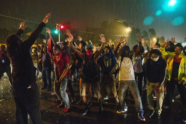 Protesters defying a curfew on the streets of Ferguson, Missouri, raise their arms in the gesture they claim teenager Michael Brown made before being shot dead by police. (Reuters)