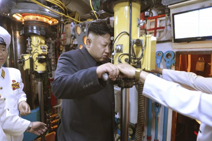 Kim Jong Un looks through a submarine periscope