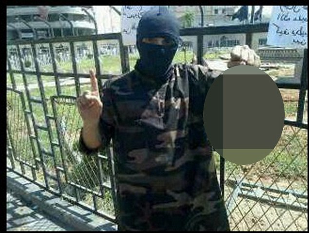 The photograph shows masked former rapper Abdel-Majed Abdel Bary, 23, holding the decapitated head while standing in Raqqa's central square