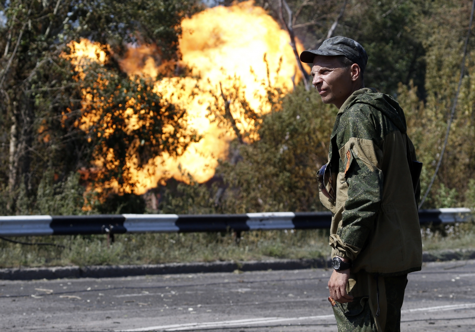 An armed pro-Russian separatist looks as flames erupt from a gas pipeline after a shelling in Donetsk