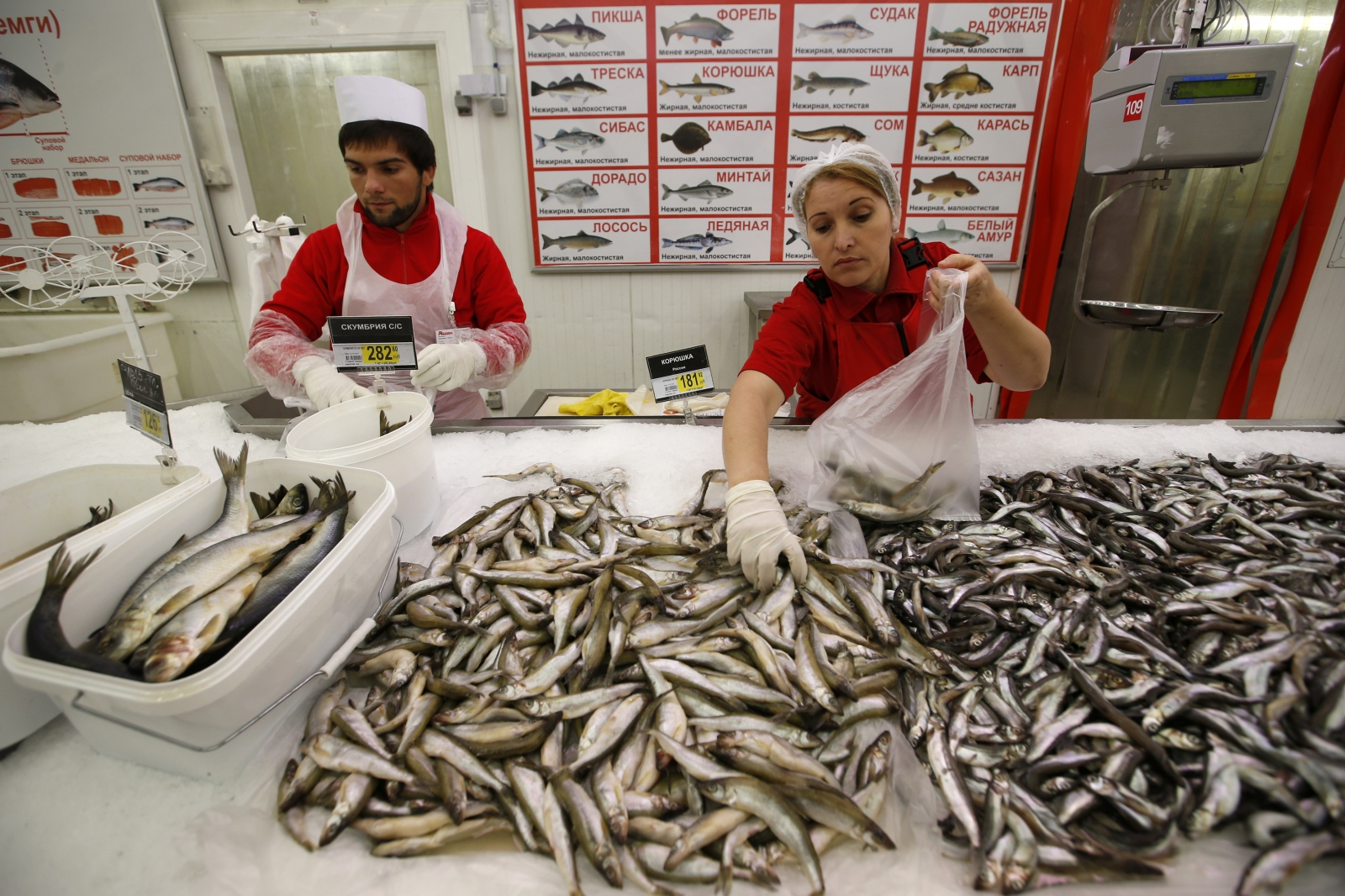 Employees work at the seafood department of an Auchan grocery store in Moscow, August 18, 2014.
