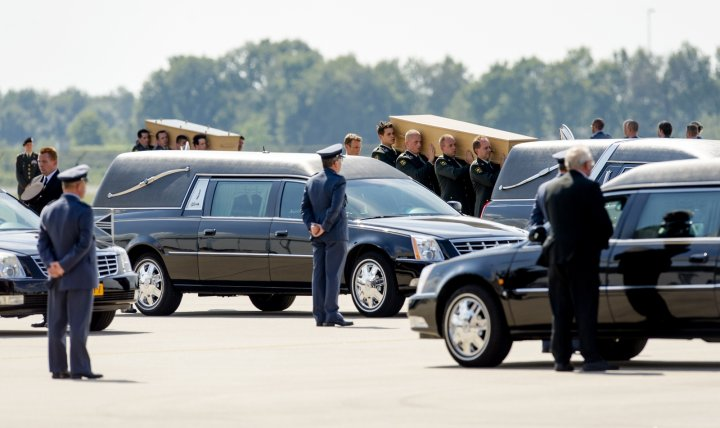 Dutch military personnel carry coffins containing victims of the MH17 crash to waiting hearses at Eindhoven Airport