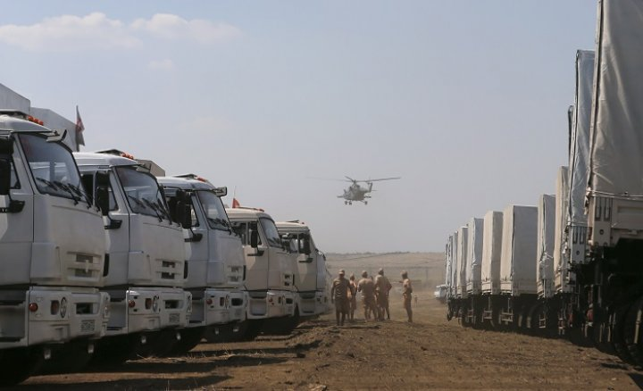 A military helicopter flies above the Russian convoy of trucks carrying humanitarian aid for Ukraine.