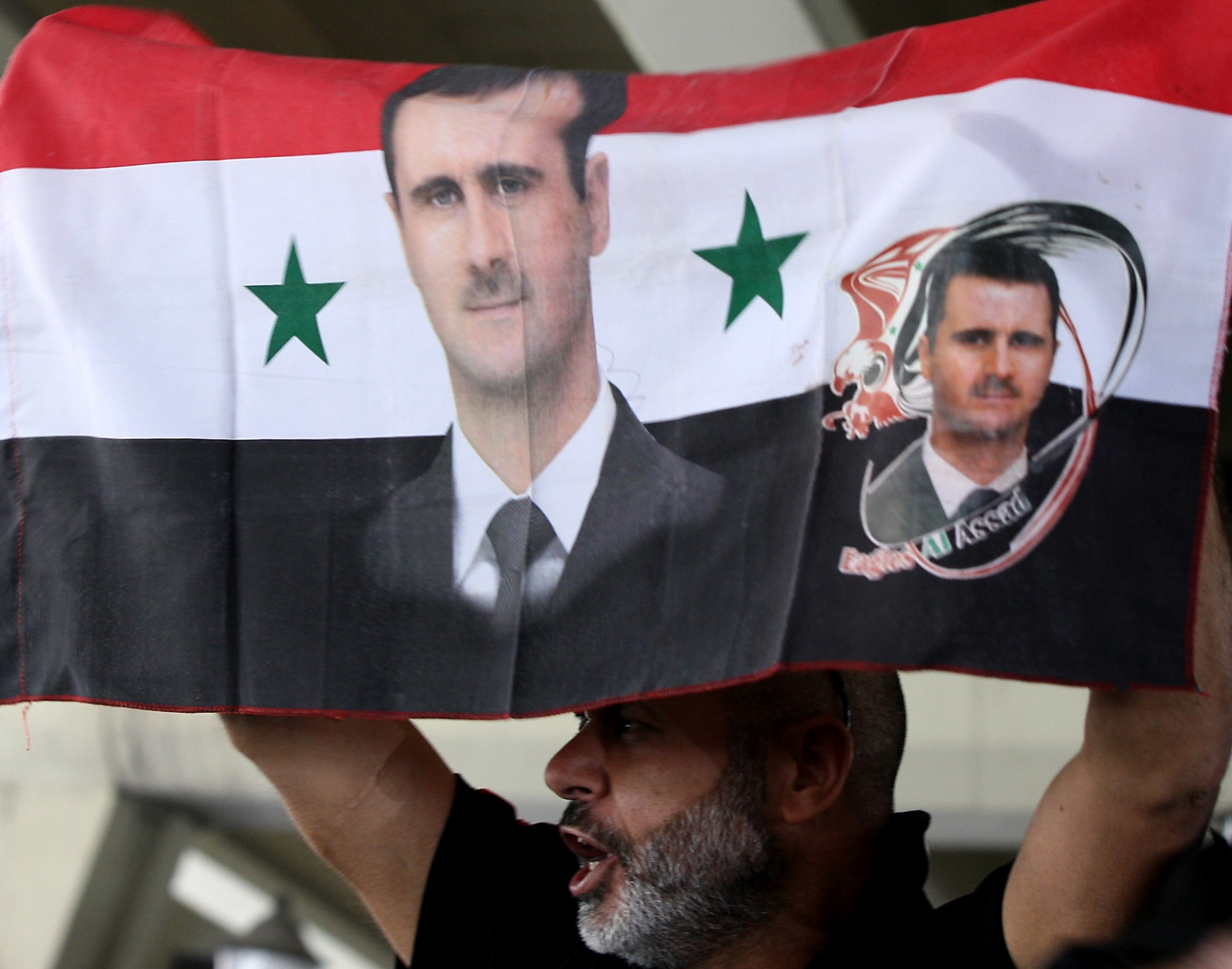 A Syrian man holds his national flag bearing pictures of Syrian President Bashar al-Assad during a pro-regime protest  in Damascus (Getty)