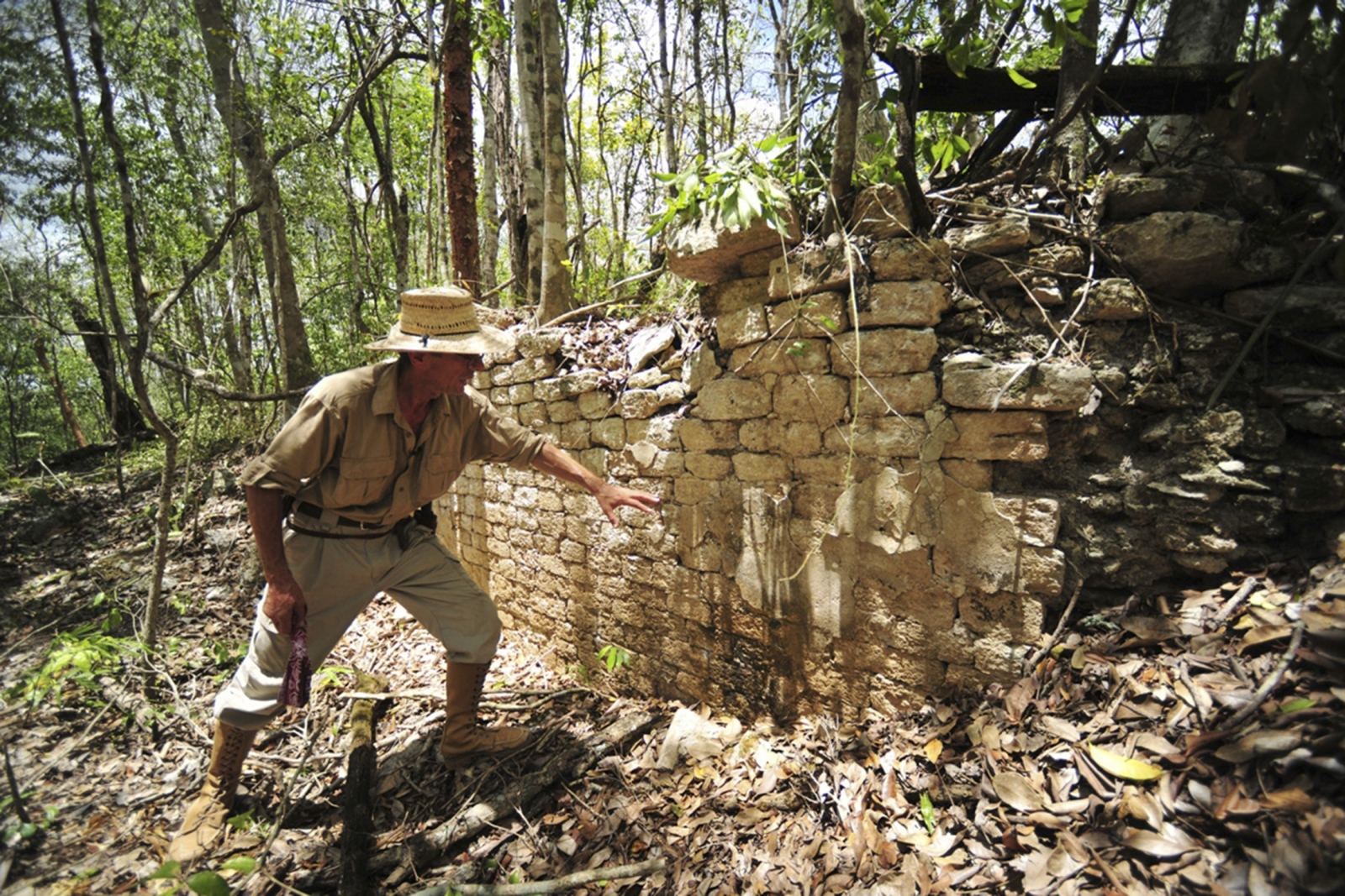 A National Institute of Anthropology and History (INAH) worker shows the remains of a building at the newly discovered ancient Maya city Chactun in Yucatan peninsula