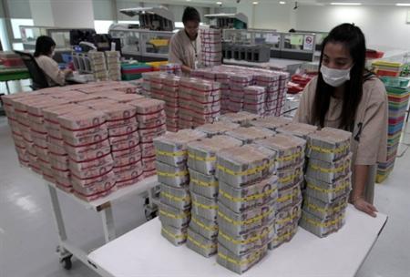 A bank employee gathers Thai baht notes at Kasikornbank in Bangkok.