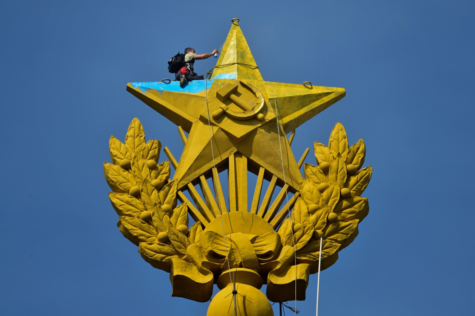 A worker paints over the star on Moscow's Stalin-era skyscraper. (AFP KIRILL KUDRYAVTSEV)