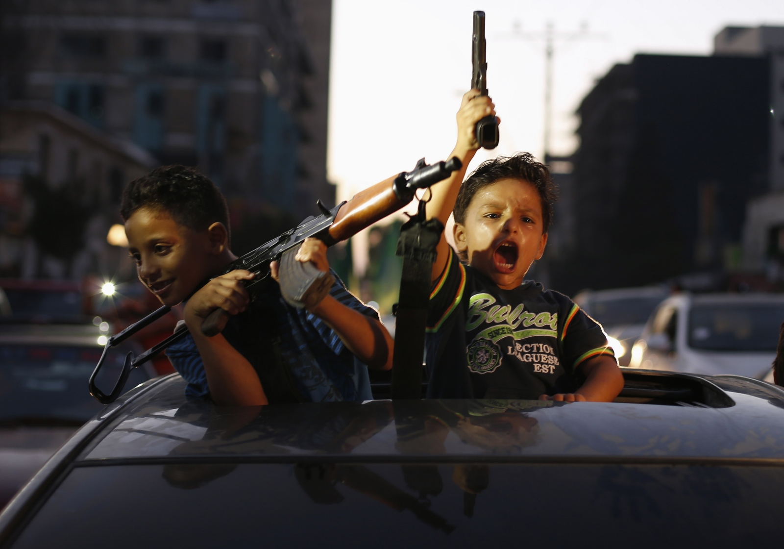 Young boys brandishing apparently real guns celebrate peace for Gaza in a Israel / Palestine ceasefire