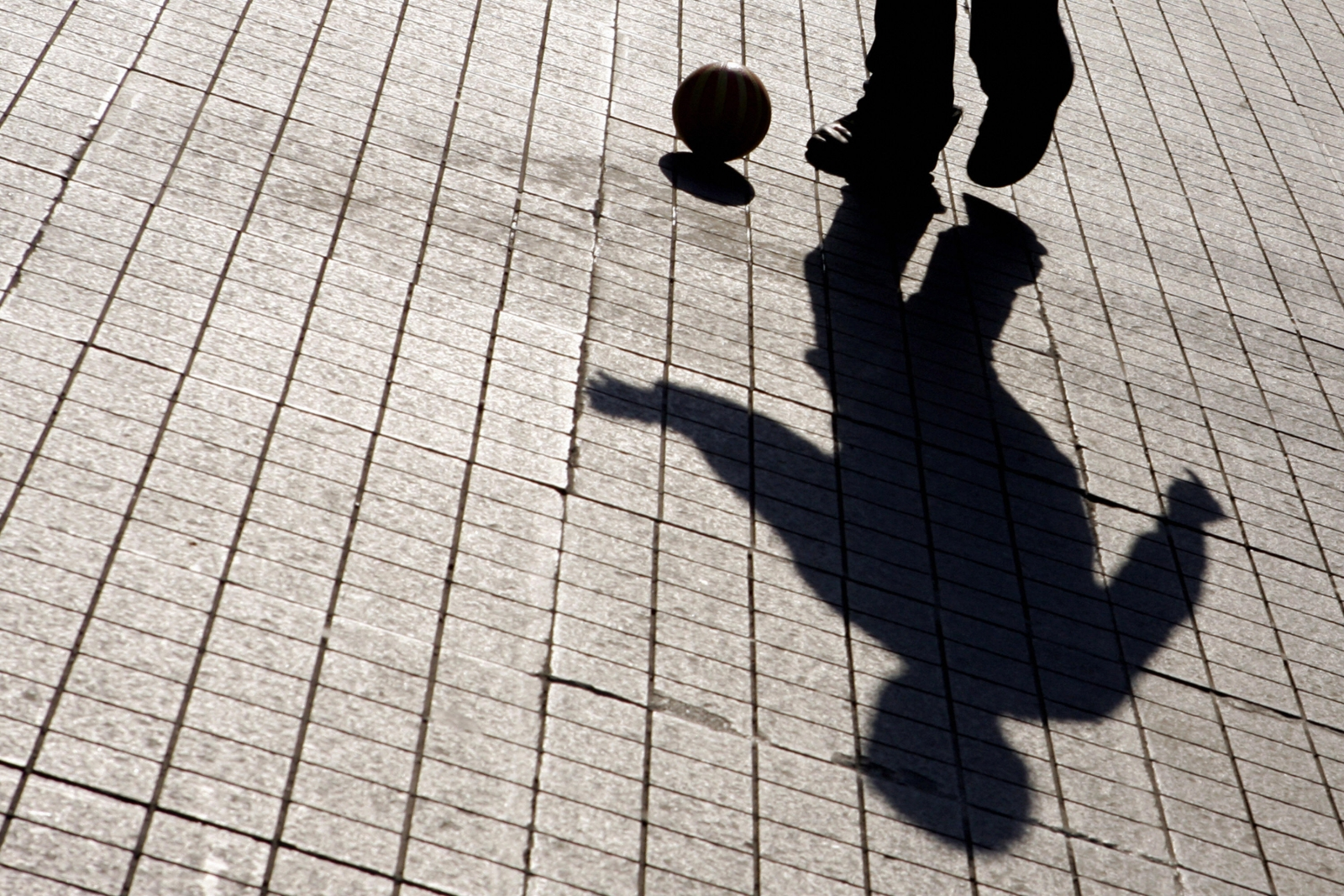 boy playing with ball in shadow
