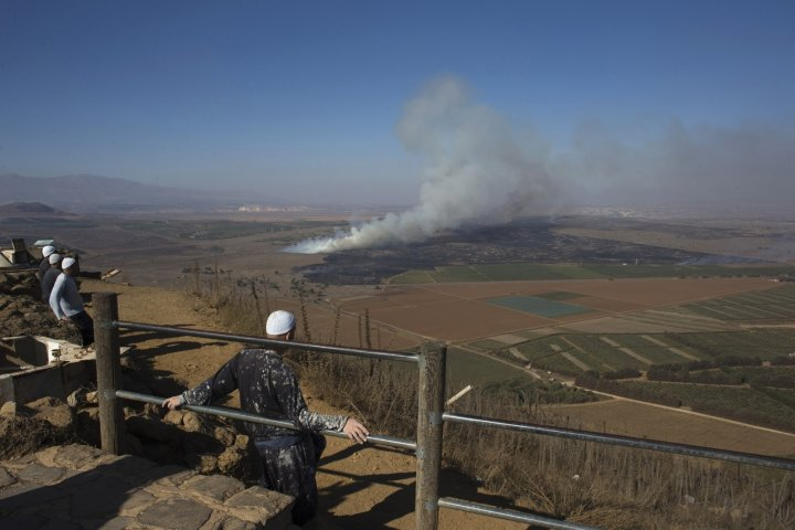 Druze men look at smoke rising on the Israeli-controlled side of the line dividing the Israeli-occupied Golan Heights from Syria following fighting near the Quneitra border crossing