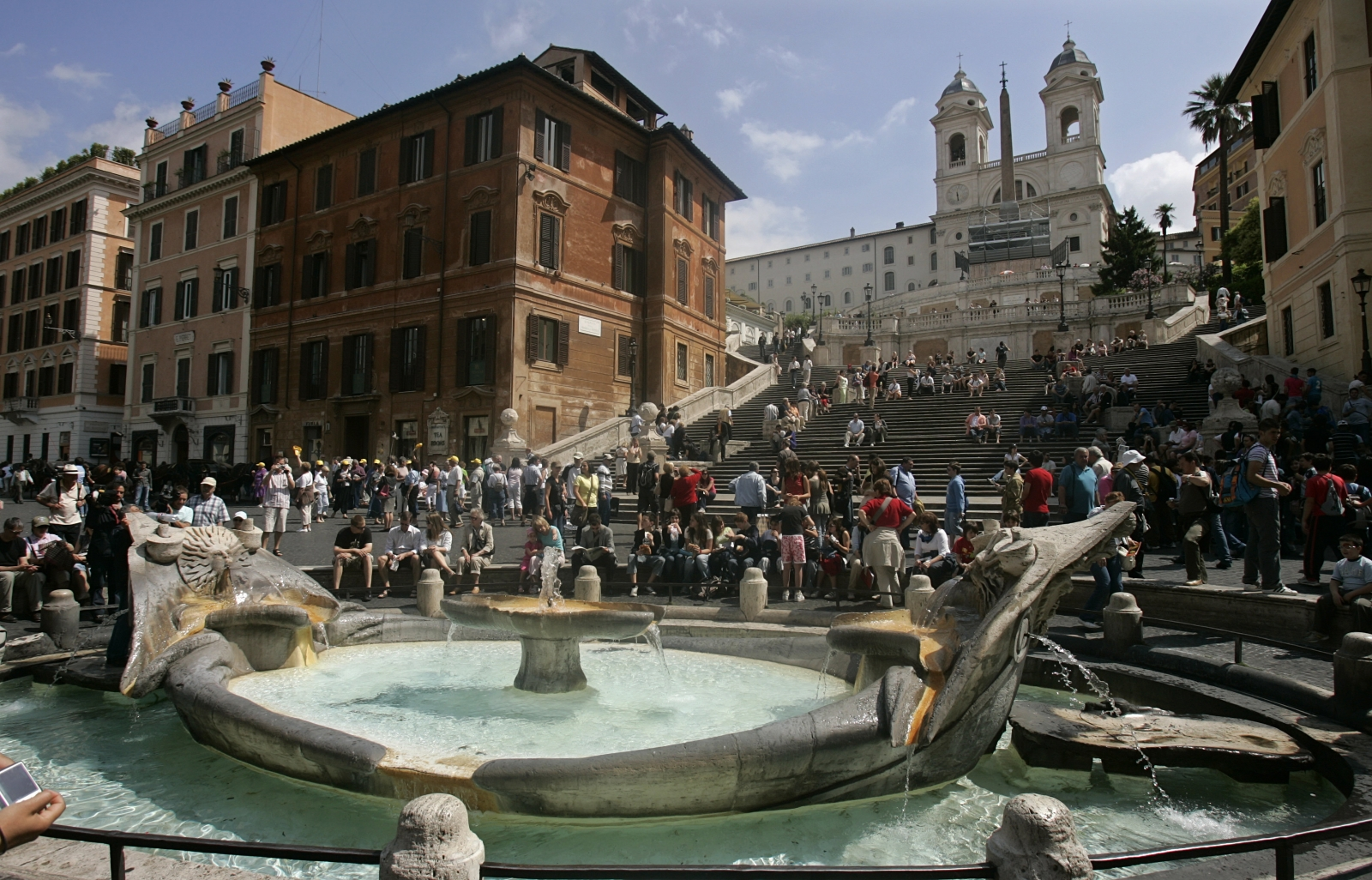 Tourists crowd about the famed Fontana della Barcaccia (Fountain of the Old Boat) at the foot of the Spanish Steps in Rome