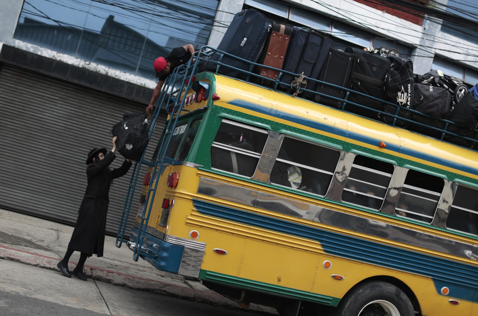 A man from the Lev Tahor loads bags onto a bus as the community depart San Juan La Laguna. (Reuters)