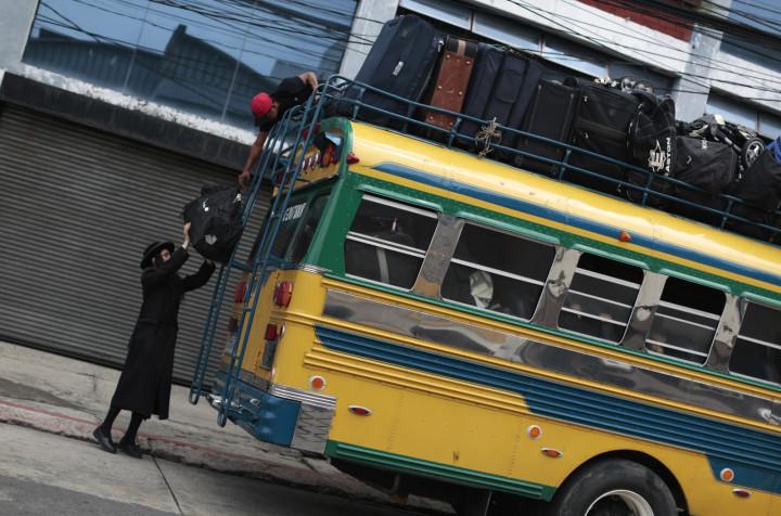 A man from the Lev Tahor loads bags onto a bus as the community depart San Juan La Laguna. (Reuters)