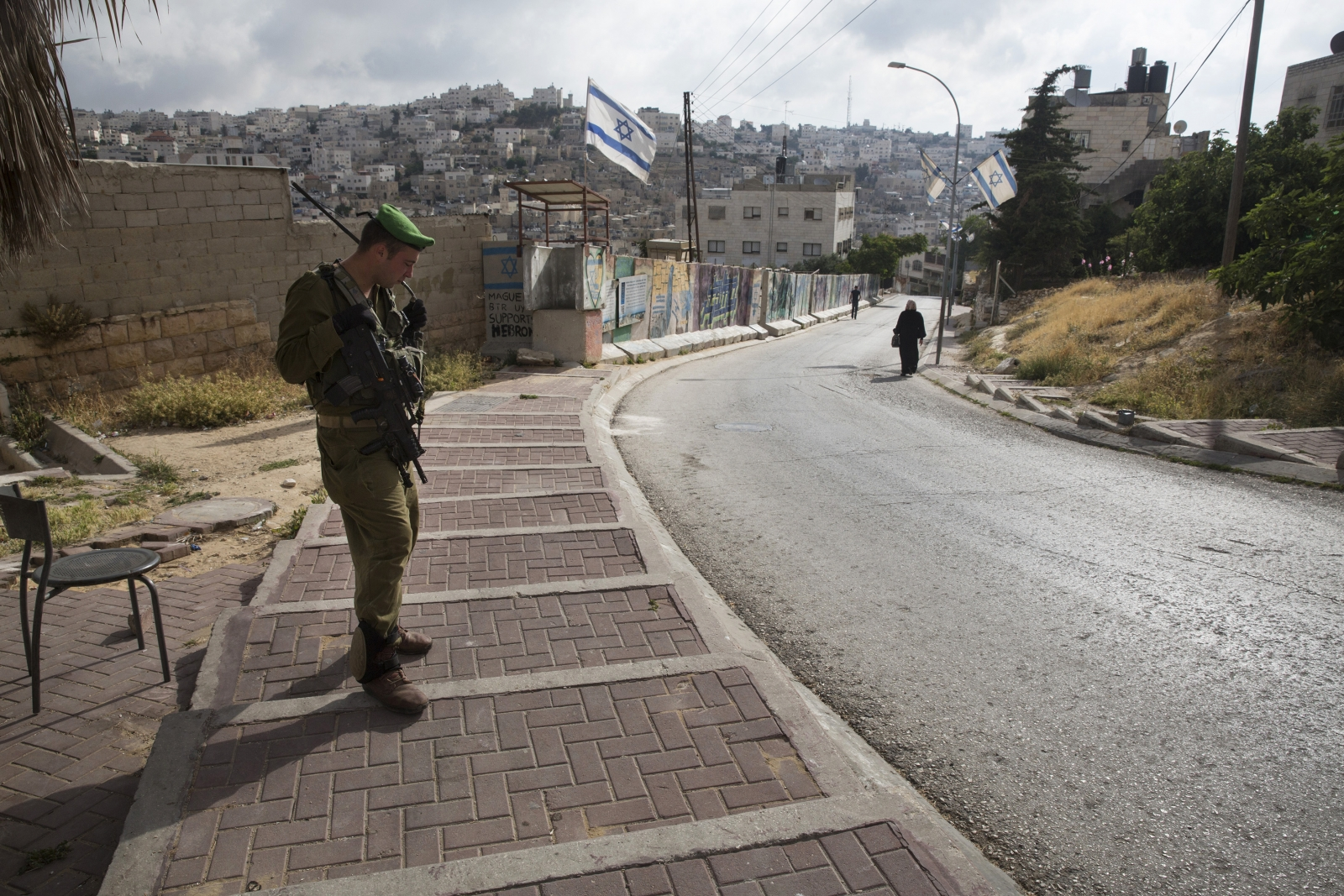 Israeli soldier guards a West Bank settlement