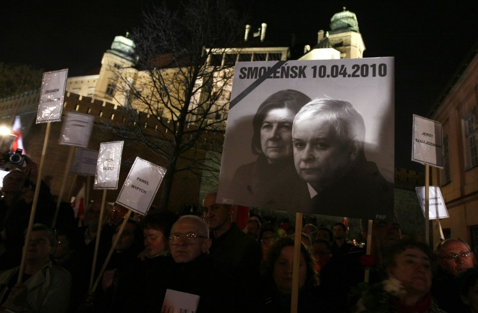 People hold a picture of late Polish President Kaczynski and his wife Maria during an event commemorating the first year anniversary of their funeral in downtown Krakow