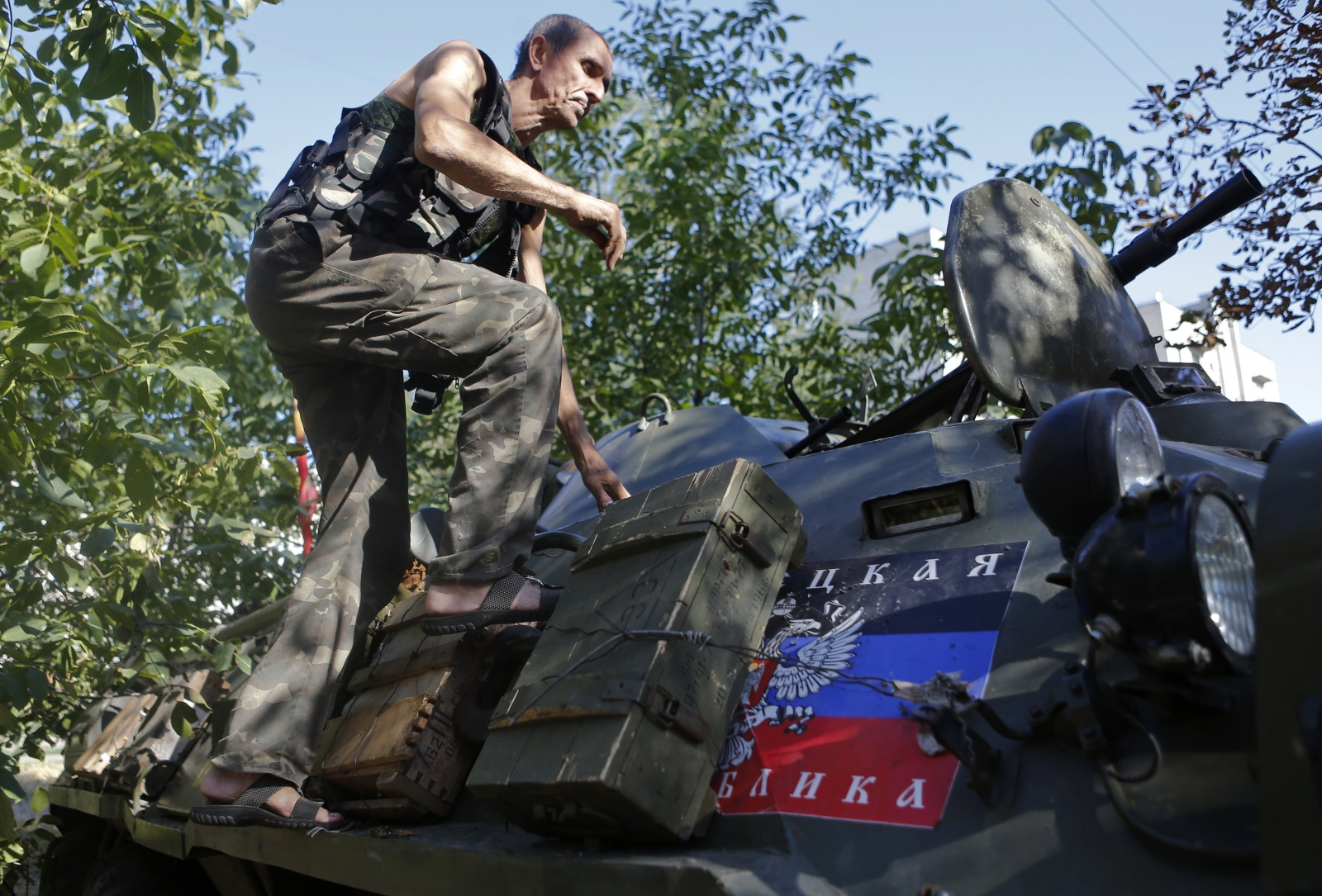 A pro-Russian separatist climbs atop an armoured personnel carrier as he guards a position in the eastern Ukrainian town of Ilovaysk