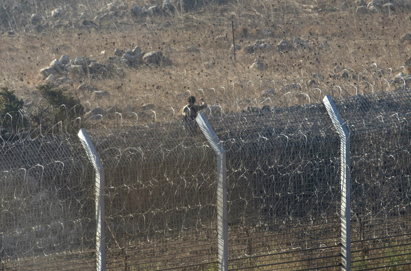 A rebel fighter is seen during a battle with Syrian army soldiers in Syria near the border fence with the Israeli-occupied Golan Heights