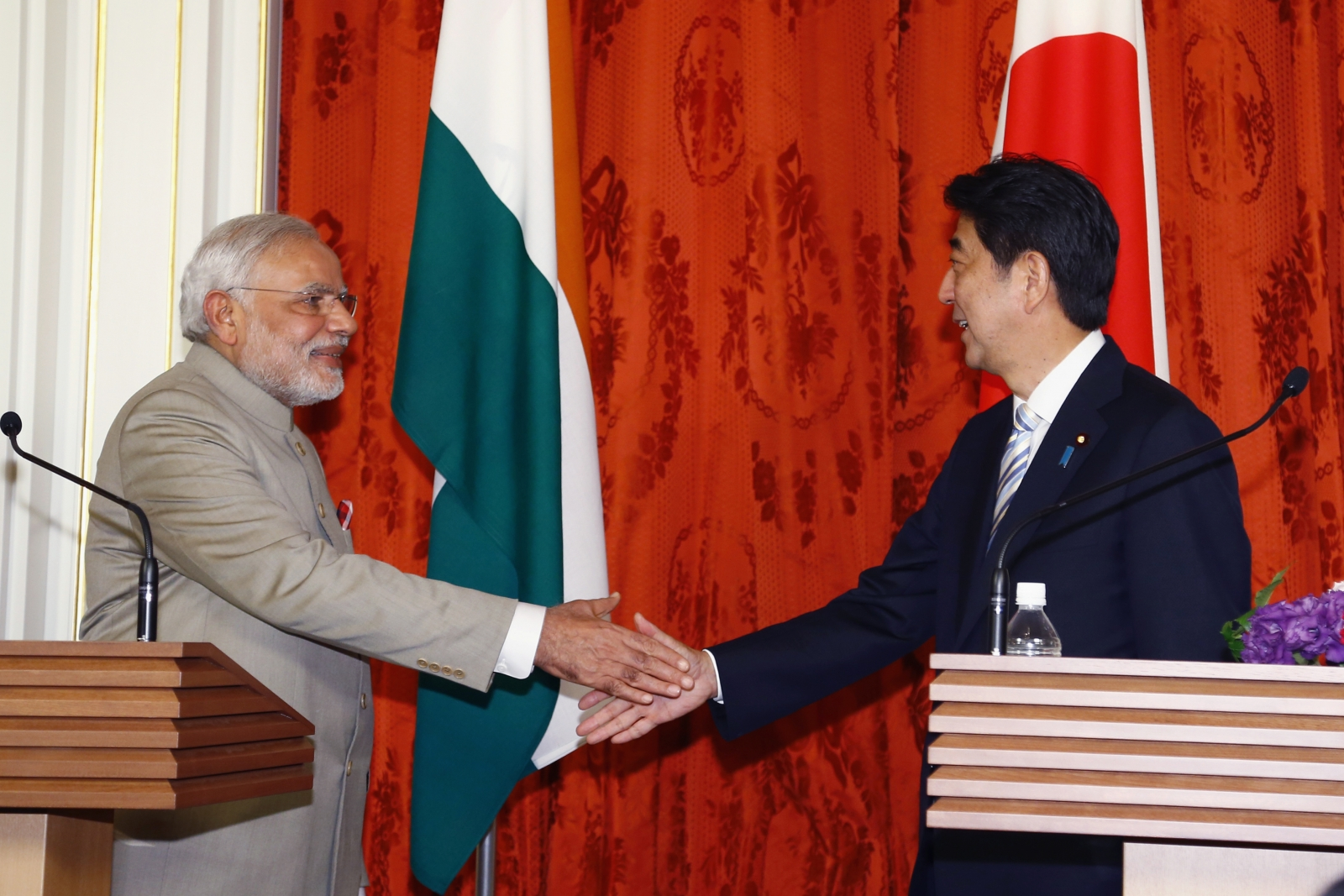 India's Prime Minister Narendra Modi (L) shakes hands with Japan's Prime Minister Shinzo Abe