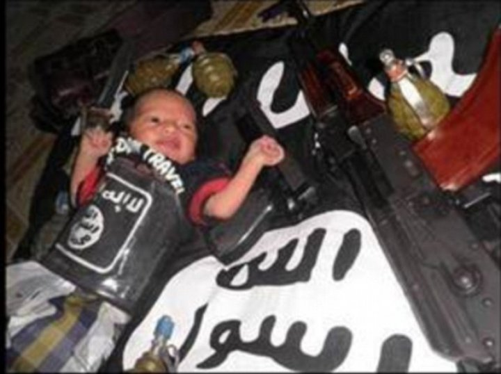 Photo showing baby surrounded by guns and grenades while wrapped in the black flag of IS
