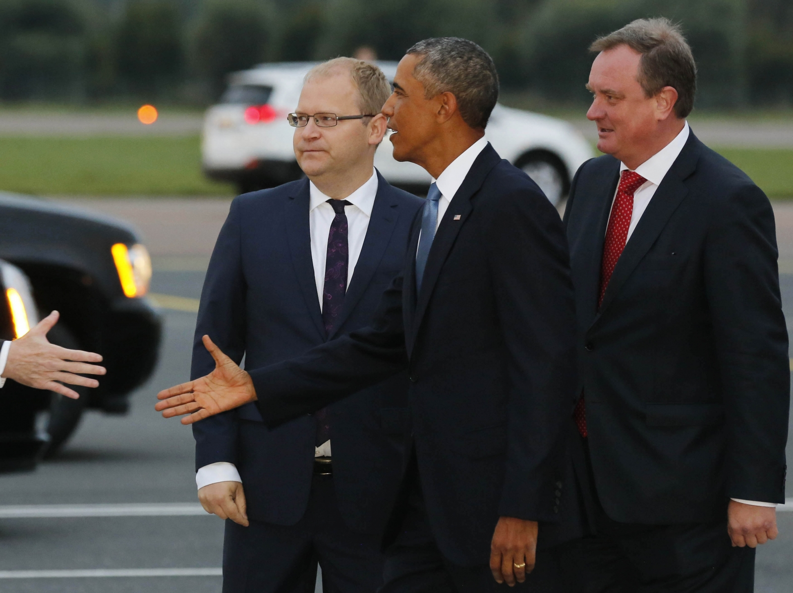 .S. President Barack Obama is greeted by Estonia Foreign Minister Urmas Paet (L) and Chief of Protocol Toomas Kahur (R)