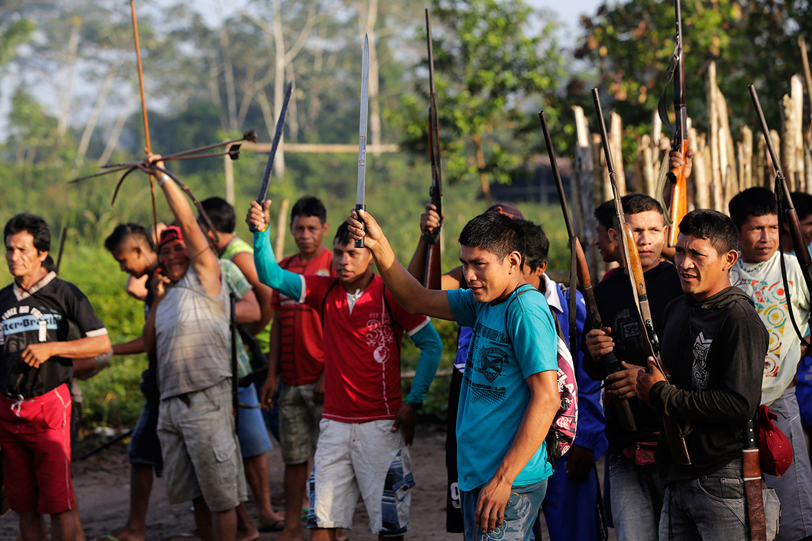 Ka'apor warriors raise their weapons as they leave the village of Waxiguy Renda to look for loggers in the Amazon