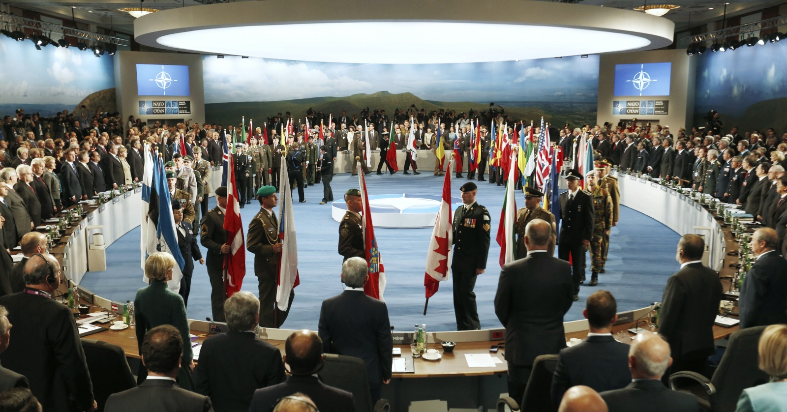 Leaders watch their flags as they participate in a NATO Summit Session One