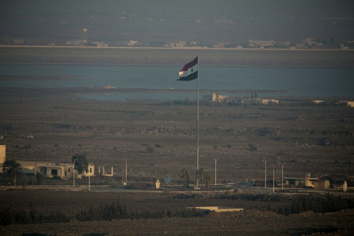 A Syrian flag flutters on a pole near the Quneitra crossing in Syria close to the border fence with the Israeli-occupied Golan Heights