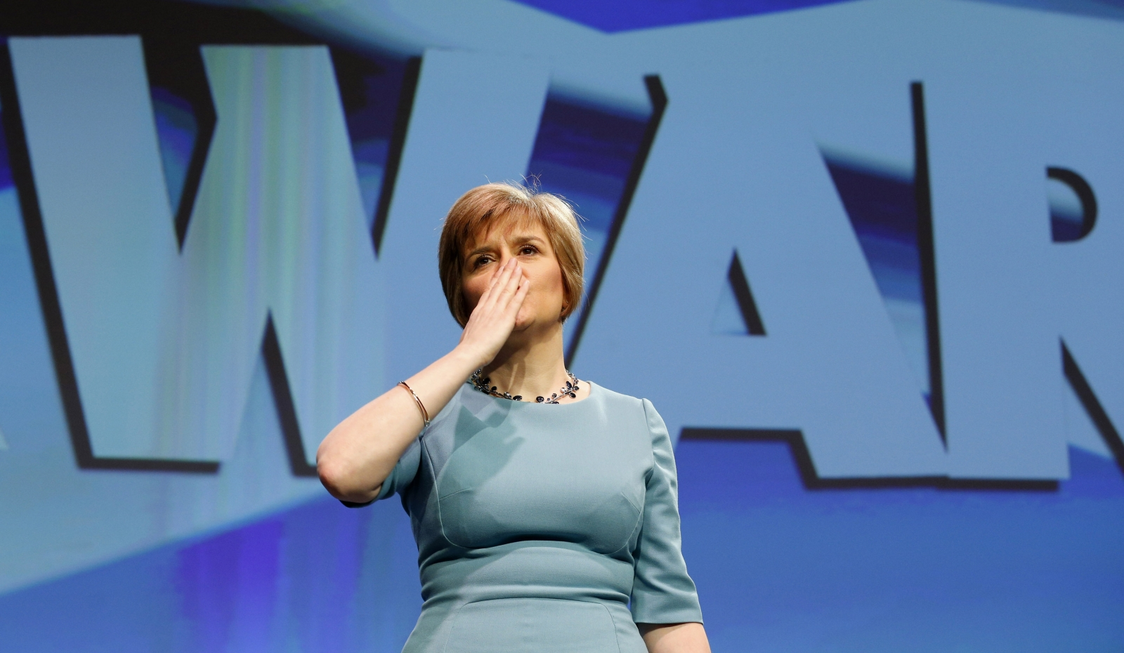 Scotland's Deputy First Minister Nicola Sturgeon blows a kiss following a speech in front of a Forward banner