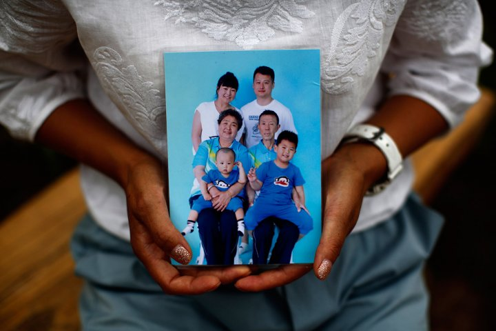 Cheng Liping shows a family photo featuring her missing husband.  Cheng said her life has been totally changed since the incident. Their two sons, who don't know about the missing plane, keep asking her when their dad is coming bac
