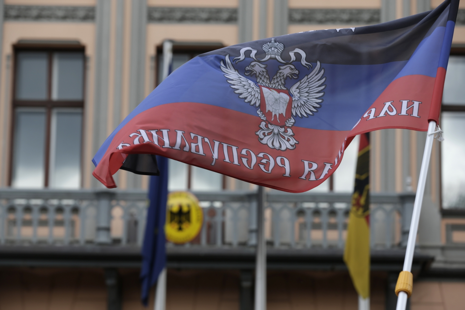 A protester waves a self-declared Donetsk People's Republic flag in front of Germany's embassy in Riga, May 8, 2014. About 40 people from the Latvian Russian Union staged a protest denouncing Ukraine's government military actions against pro-Russian se